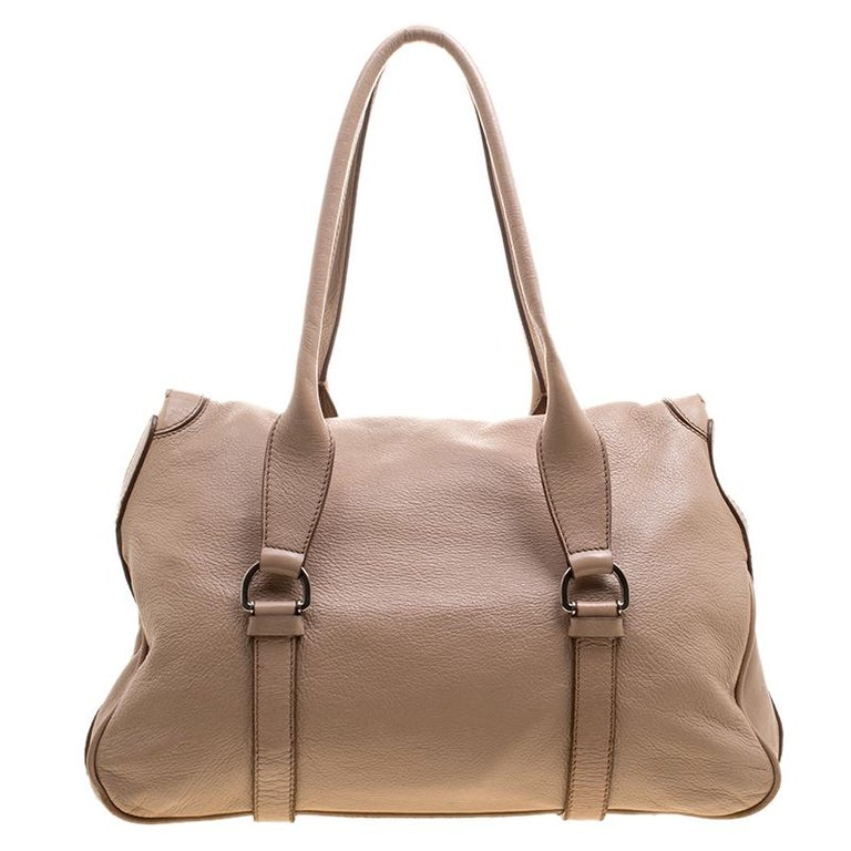 A truly posh and elegant piece to add to your collection. This Boston bag by Celine is crafted from beige leather and styled with a flap that reveals a spacious fabric interior to house your essentials. Held by two handles, this bag works well for