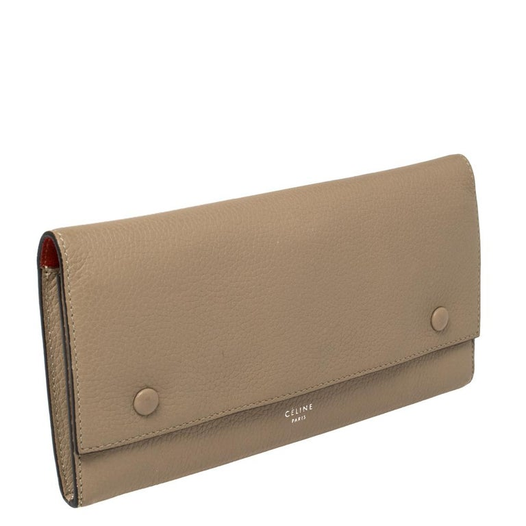 This Celine wallet is built for making a statement. Crafted from leather, it has a beige exterior and a front flap that opens to a leather and fabric interior housing a zip pocket and multiple card slots. It will surely prove to be an amazing buy!