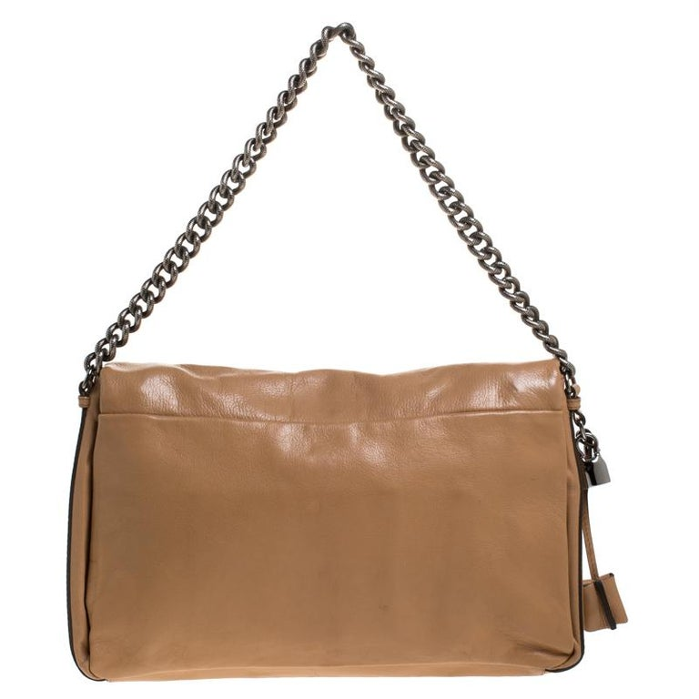Every woman needs a bag that is pretty and functional, just like this shoulder bag from Celine. Crafted from leather, it has been styled with a flap leading to a spacious nylon interior and it is held by a chain handle. This is definitely one handy