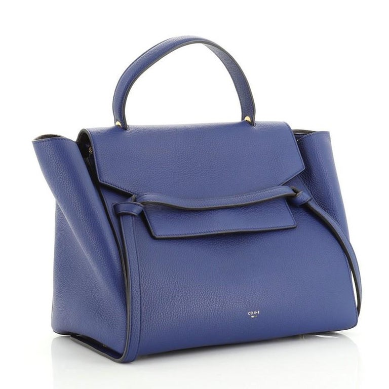 This Celine Belt Bag Grainy Leather Mini, crafted from blue grainy leather, features single looped top handle, exterior back zip pocket, and gold-tone hardware. Its top zip closure opens to a blue suede interior.   Estimated Retail Price: