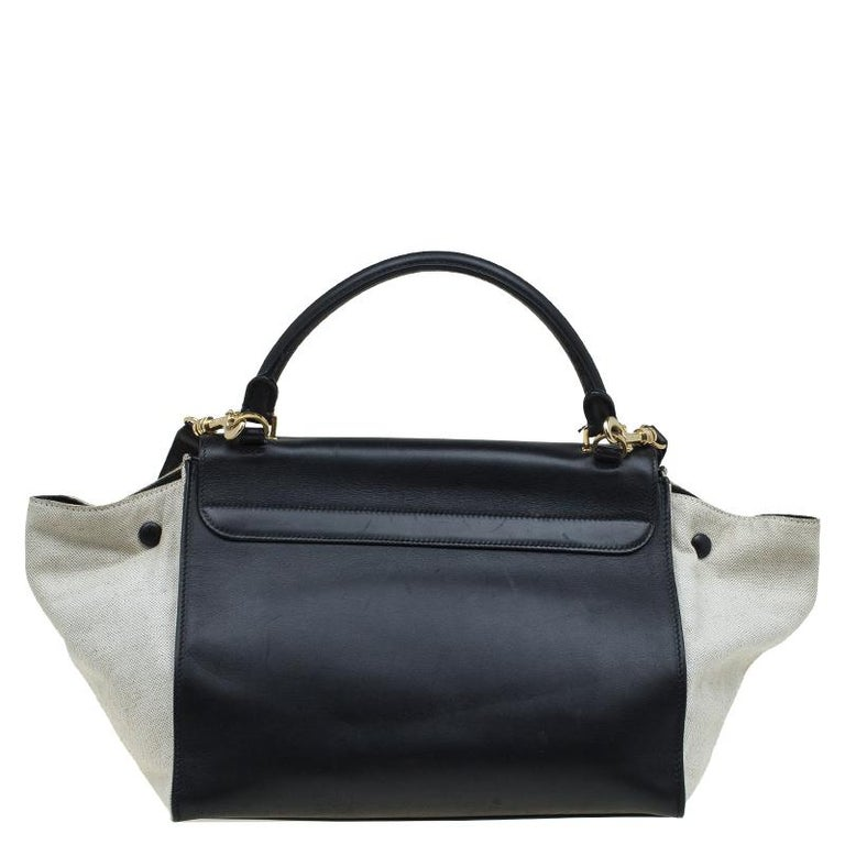 Made in Italy, this stylish Celine handbag is crafted in black and beige leather. It has gold-tone hardware, a top handle and a detachable shoulder strap for an easy carrying experience. The zip top closure opens to a leather lined interior and can