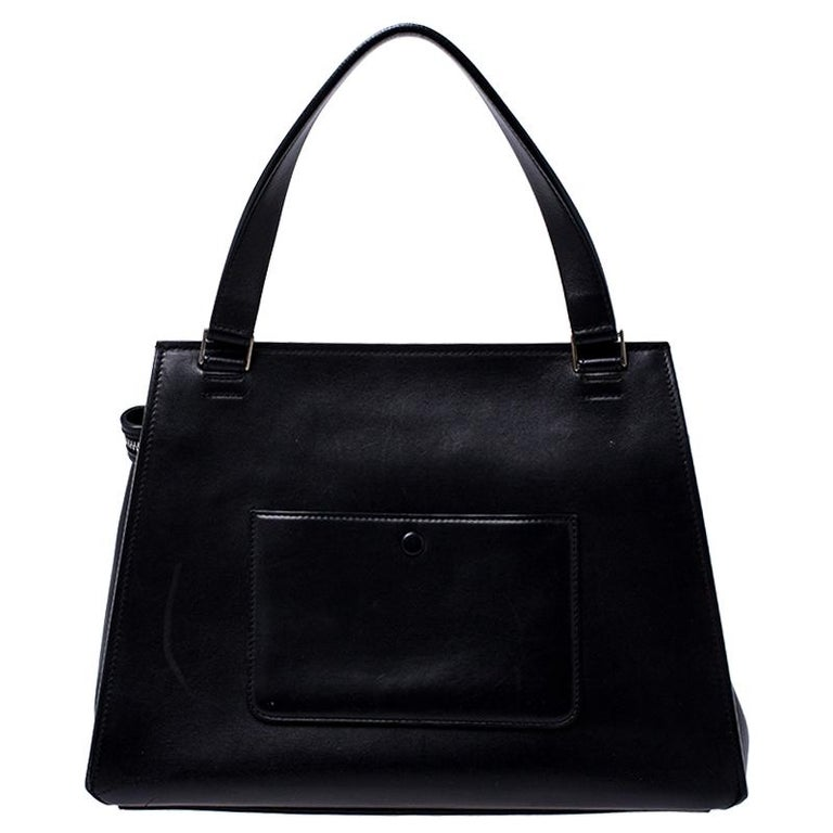 This Celine Edge bag is not only visually magnificent but also functional. It has been crafted from leather and styled with a silhouette that is classy and posh. The black and grey bag has a top handle and a top zipper that reveals a spacious