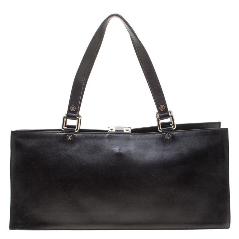 Carry your daily essentials in this black bag by Celine. Crafted from subtle leather, this petite tote is designed in a structured silhouette and is detailed with a buckle flap at the front. The interior is lined with canvas and features a zip