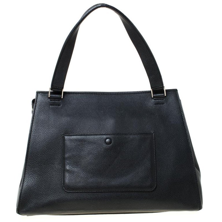 This Celine Edge bag is not only visually magnificent but also functional. It has been crafted from leather and styled with a silhouette that is classy and posh. The black bag has a top handle and a top zipper that reveals a spacious interior. The