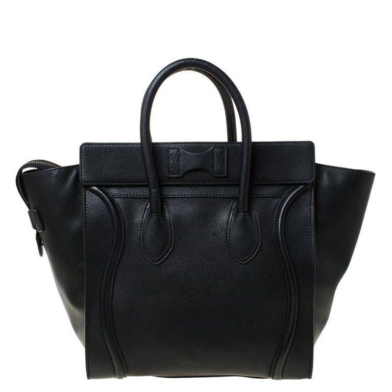 The iconic Mini Luggage tote from the house of Celine has had a cult following ever since its introduction. Featuring a chic trapeze shape, this bag is crafted in black leather with wings, two rolled top handles and is secured with a top zip
