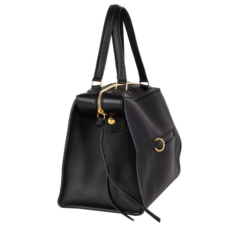Céline 'Small Ring' handbag in black smooth calfskin with a ring zip pocket at front featuring gold-tone hardware. Opens with a zipper on top and is lined in midnight blue suede with one zip pocket against the back and two slit pockets attached. Has