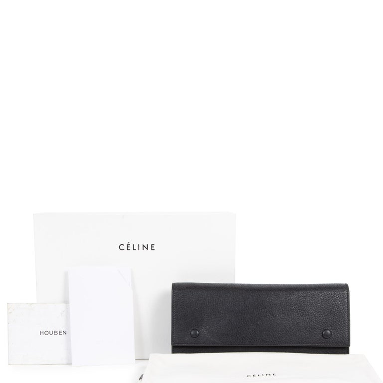 Good preloved condition.  Celine Black Leather Wallet  This gorgeous wallet by Celine has a fun touch to it. The exterior is crafted out of smooth black leather, has an open pocket on the back, and features the brands name in silver-tone letters on