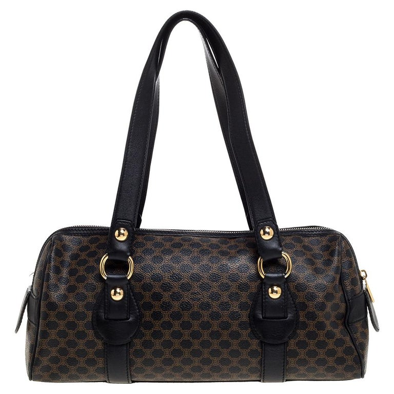 This Celine satchel is a symbol of style and reliability. This black bag is crafted from Macadam coated canvas and leather. It is equipped with a spacious fabric interior, two handles and gold-tone hardware.