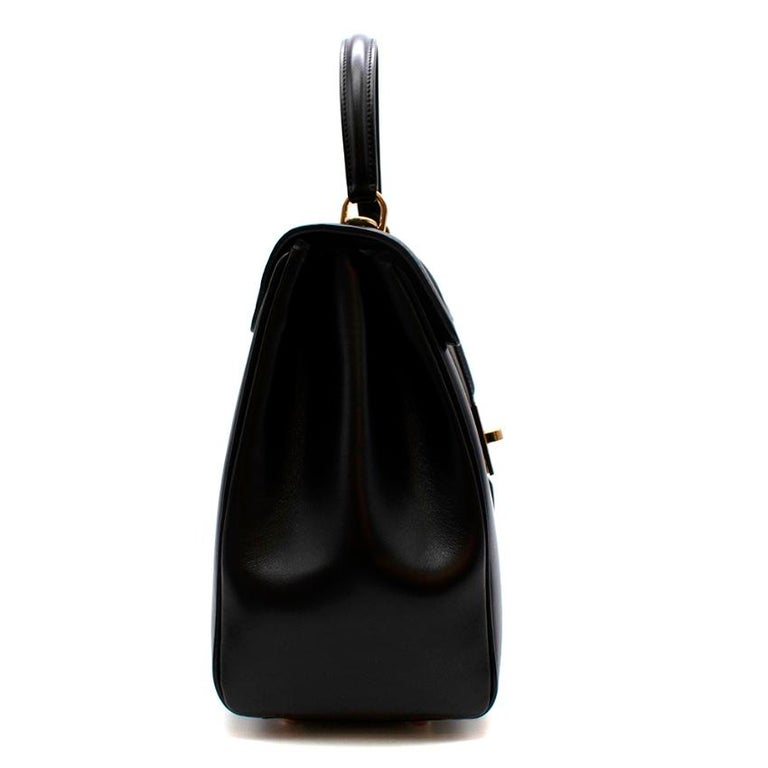 Celine Black Satinated Calfskin Medium 16 Bag  The 16 was designed by Hedi Slimane on the first day of his arrival at Celine. A design that is based on the very parisian way of wearing a bag. The 16 recaptures the codes of some of the maison