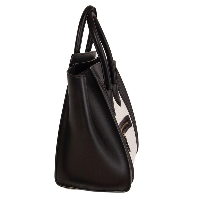 Céline 'Mini Luggage' tote in black and white large grained calfskin featuring outer zipper pocket on the front. Lined in black calfskin with one zipper pocket against the back and two open pockets against the front. Has been carried and is in