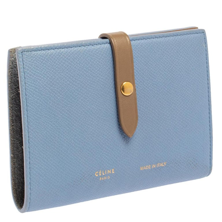 This Celine wallet is built for making a statement. Crafted from leather, it has a blue and brown exterior and a buttoned strap on the front that opens to a leather and fabric interior housing a zip pocket, slip pockets, and multiple card slots. It