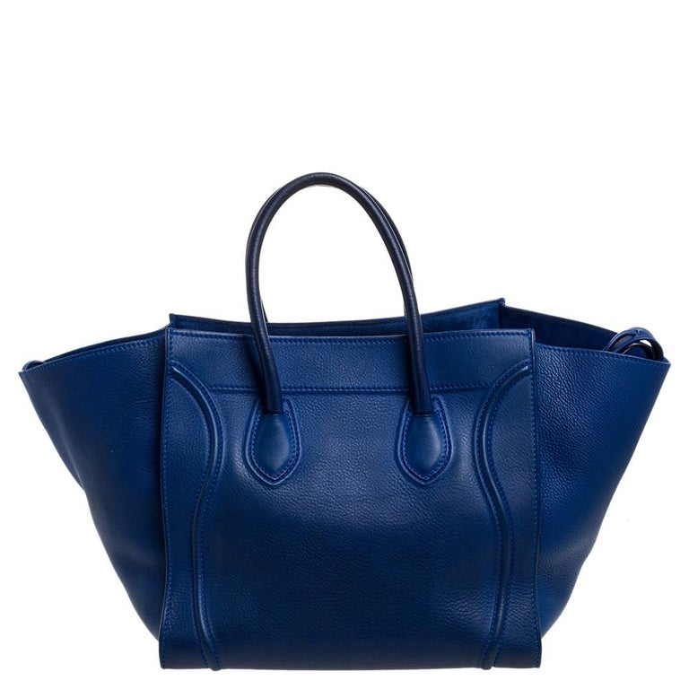 Celine released the Phantom as a newer version of its successful Luggage model. Unlike the Luggage toes, the Phantom has an open-top, wider wingspans, and a braided zipper pull. We have here the one in leather. It has two top handles, a blue shade,