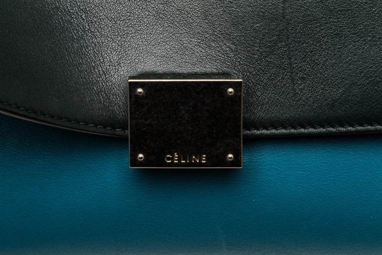 Blue leather Celine Trapeze Bag with silver-tone hardware, single rolled top handle, dual gray nubuck side gussets with snap expansions, exterior zip pocket at back, tonal leather lining, dual interior slit pockets and flip-lock closure at dark