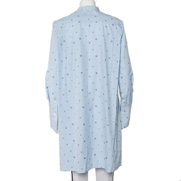 Tailored beautifully using cotton, this oversized shirt dress from Celine will be a fashionable addition to your summer wardrobe. It has long sleeves, button closure, an asymmetric high-low hemline, and embroidered details all over its striped