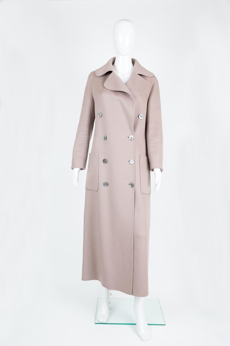 Blush color Celine 100% cashmere long coat featuring a double breasted opening, large pockets, front logo button fastening, a separated belt, very light as it is an unlined coat.  Estimated size 40fr/US8/UK12 Composition: 100% cashmere,  In