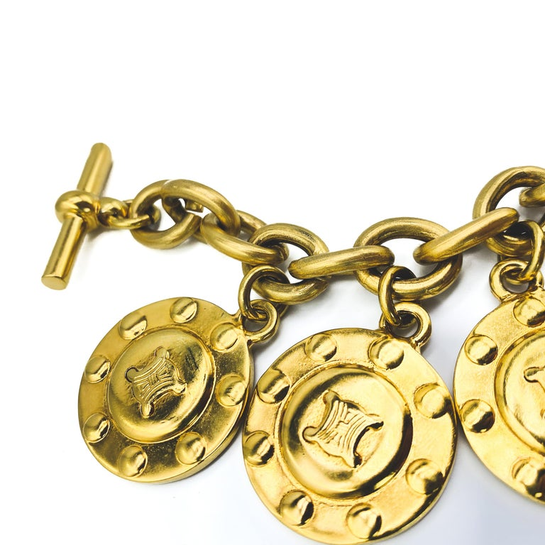 Celine Vintage 1980s Charm Bracelet Incredible statement charm bracelet from the iconic house of Celine  Detail -Made in Italy in the 1980s -Crafted from high quality gold plated metal -Large circular charms on a chunky chain bracelet with a toggle
