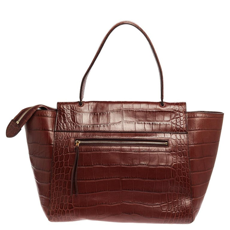 Designed in a gorgeous shape, this Belt Bag by Celine is a great style enhancer. Crafted from croc-embossed leather, it has a tuck-in flap that opens to a spacious suede-lined interior. The brown bag is further equipped with a zip pocket at the back