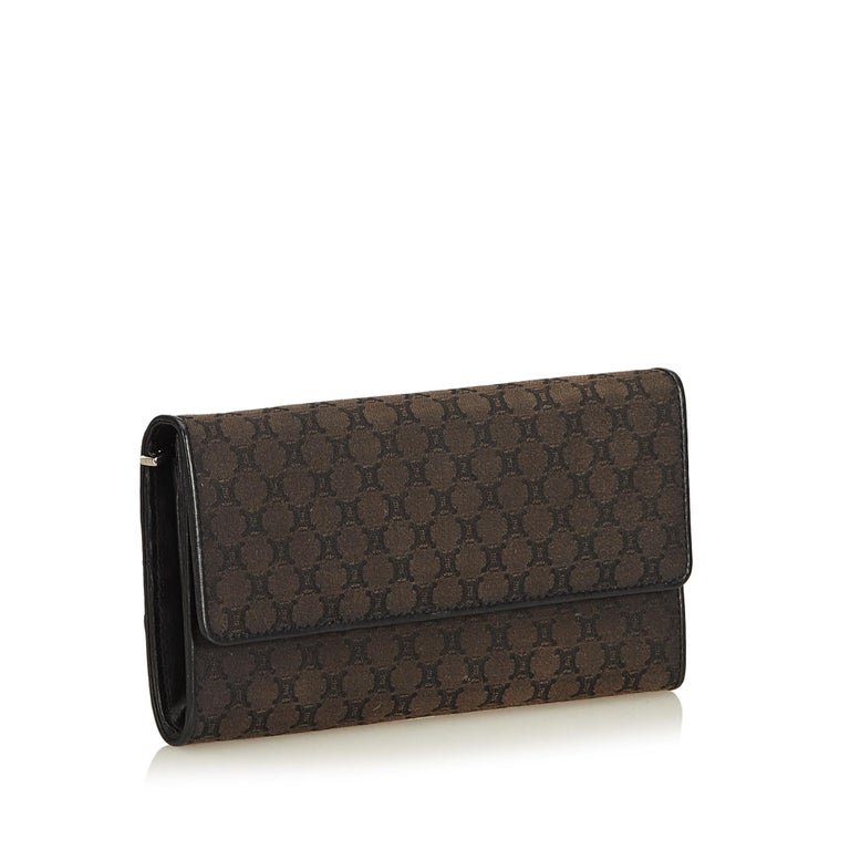 This long wallet features a jacquard body with leather trim, front flap with button clasp closure, and interior zip and slip pockets. It carries as AB condition rating.  Inclusions:  Dust Bag Box  Dimensions: Length: 10.00 cm Width: 19.00 cm Depth: