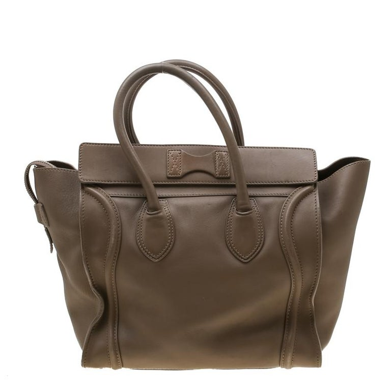 The mini Luggage tote from Celine is one of the most popular handbags in the world. This tote is crafted from leather and designed in a brown shade. It comes with rolled top handles and a front zip pocket. The bag is equipped with a well-sized
