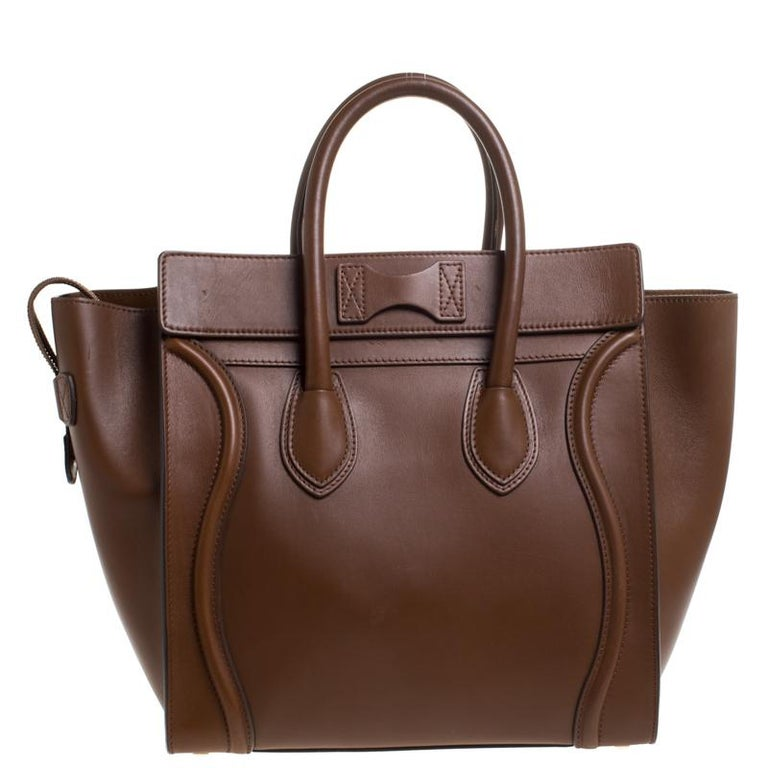 The mini Luggage tote from Celine is one of the most popular handbags in the world. This tote is crafted from leather and designed in a brown shade. It comes with rolled top handles, protective metal feet and a front zip pocket. The bag is equipped
