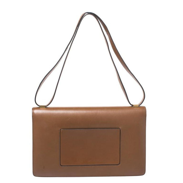 From the house of Celine comes this gorgeous Classic Box flap bag that will perfectly complement all your outfits. It has been luxuriously crafted from leather and styled with a flap that opens to a well-sized leather interior. The bag is high on