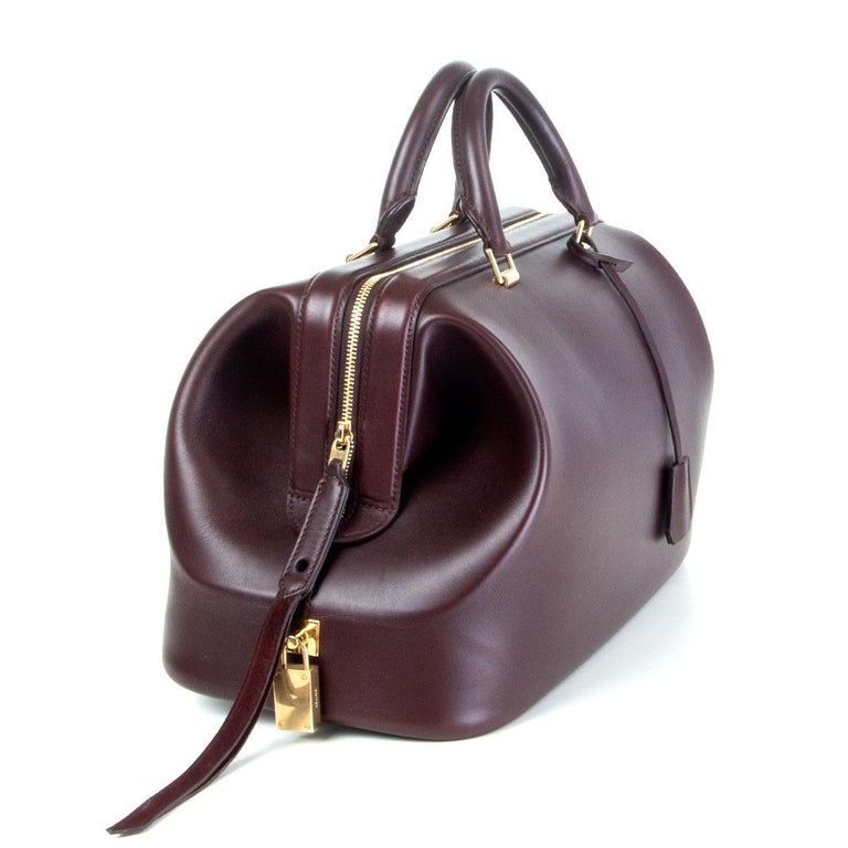 authentic Céline Frame Doctor Small handbag in deep burgundy calfskin. Opens with a zipper on top and is lined cognac calfskin with one open pocket against the back and six small open pockets against the front. Has been carried and is in excellent