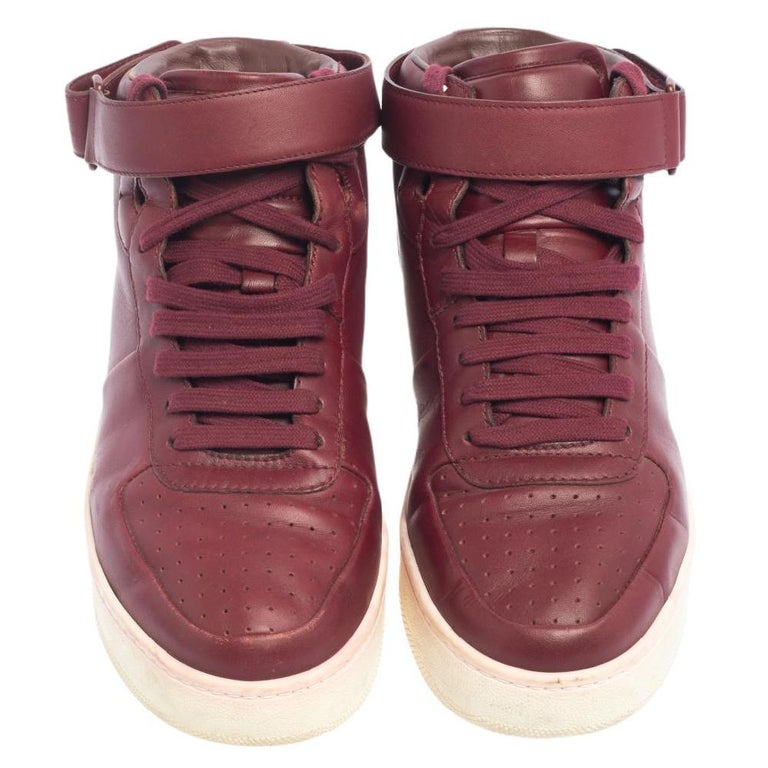One's wardrobe is incomplete without a good pair of sneakers! If you're searching for a new addition, we suggest this one by Celine. These mid-top women's sneakers have been crafted using burgundy leather and styled with lace-up closure and velcro