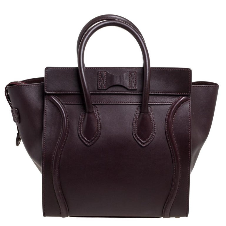 The mini Luggage tote from Celine is one of the most popular handbags in the world. This tote is crafted from leather and designed in a burgundy shade. It comes with rolled top handles and a front zip pocket. The bag is equipped with a well-sized