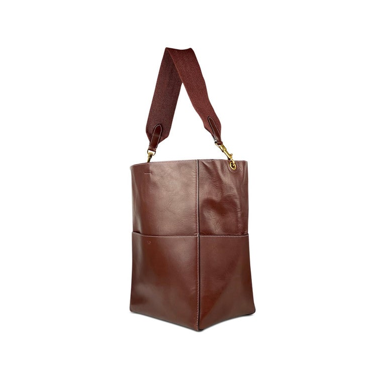 Burgundy calfskin Céline Seau Sangle bag with  - Gold-tone hardware - Single detachable flat canvas shoulder strap - Four exterior slit pockets - Tonal suede lining, dual interior pockets; one with zip closure and hook closure at top  Overall