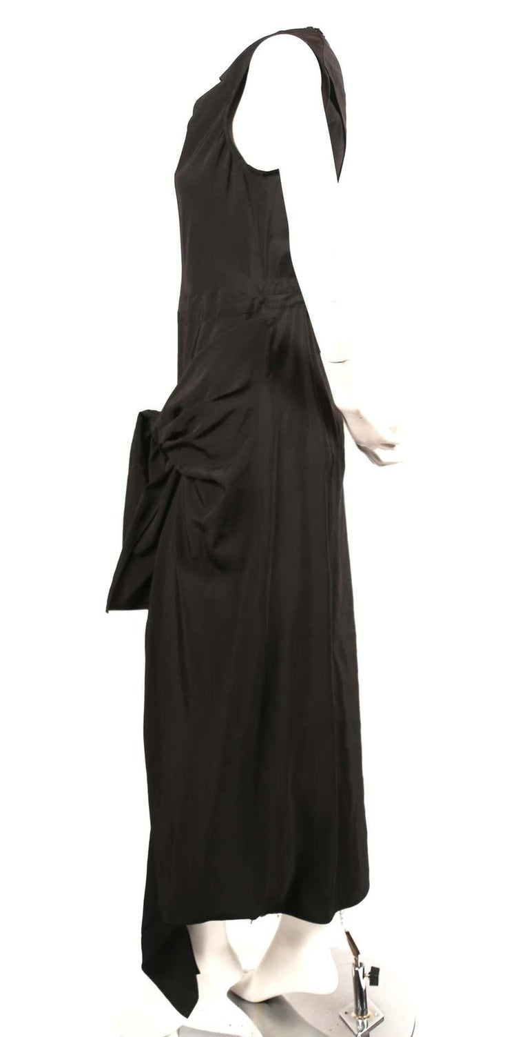 Jet-black dress with twisted neckline, ties at hips and cut out at back designed by Phoebe Philo for Celine dating to resort of 2016. Best fits a French size 40. Approximate measurements: shoulder 15