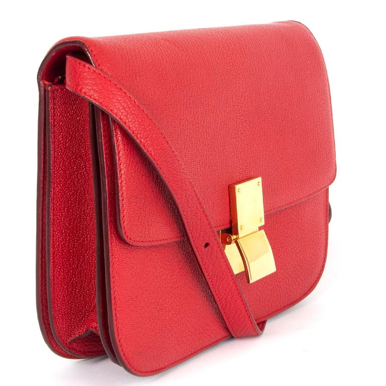 100% authentic Céline Classic Medium shoulder bag in Carmin red goatskin featuring gold-tone hardware. Opens with a push-lock on the front. The inside is divided into two compartments with two open pockets against the front and a zipper pocket