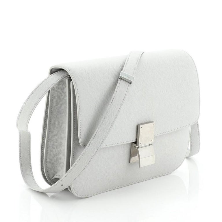 This Celine Classic Box Bag Grainy Leather Medium, crafted from gray grainy leather, features an adjustable strap and aged silver-tone hardware. Its push-tab closure opens to a gray leather interior with two open compartments, zip compartment and