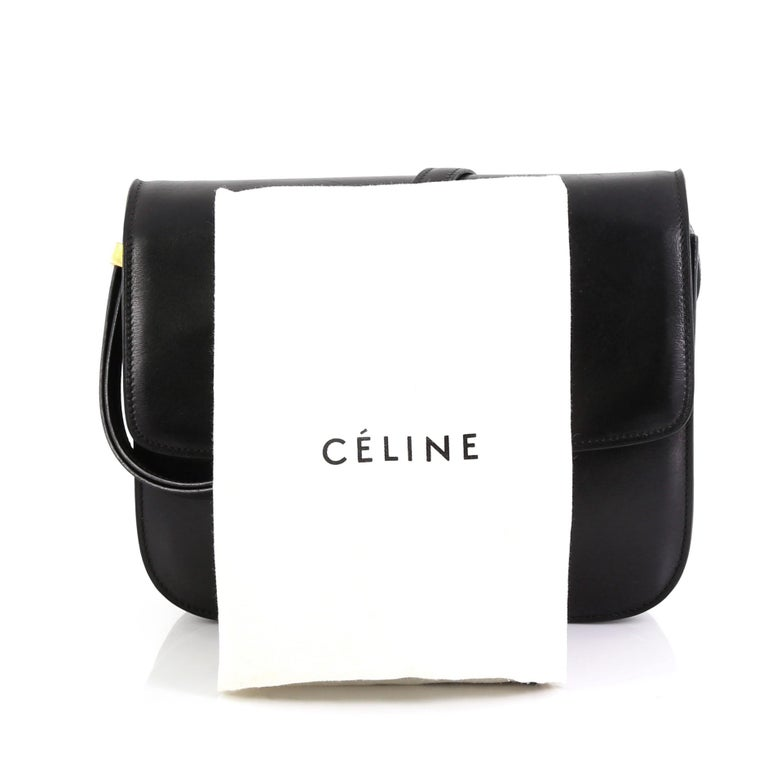 This Celine Classic Box Bag Smooth Leather Medium, crafted from black smooth leather, features a long adjustable strap and gold-tone hardware. Its push-tab closure opens to a black leather interior with two open compartments, zip compartment and