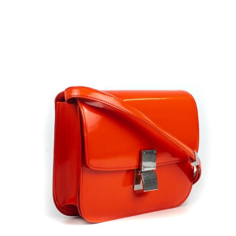 - Designer: CÉLINE - Model: Classic - Condition: Very good condition.  - Accessories: Dustbag - Measurements: Width: 20.5cm, Height: 18cm, Depth: 5cm, Strap: 92cm - Exterior Material: Patent leather - Exterior Color: Red - Interior Material: