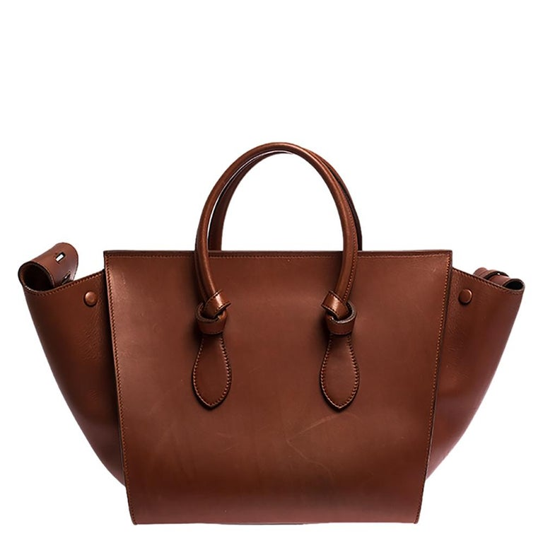 This Tie tote from Celine brings a wonderful mix of fashion and function. Expertly crafted from leather, it comes in a lovely shade with dual top handles and metal studs to protect the base. Made in Italy, it has a spacious interior lined with suede