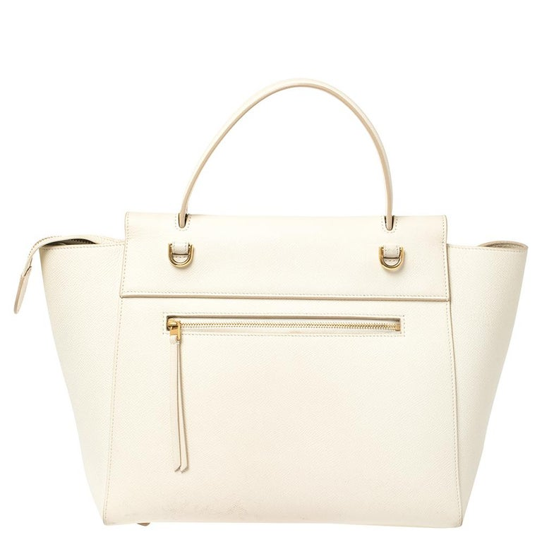 Bags from Celine are symbols of excellent craftsmanship and timeless design. This cream creation has been crafted from leather and styled with a front tuck-in flap and belt details. It flaunts a single top handle, a zip pocket at the back, and a