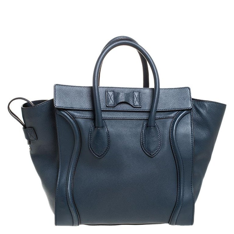 The Mini Luggage tote from Celine is one of the most popular handbags in the world. This tote is crafted from leather and designed in a dark blue shade. It comes with rolled top handles and a front zip pocket. The bag is equipped with a well-sized