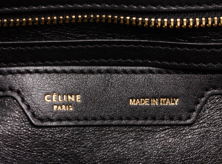 Denim Black leather Céline Medium Trapeze bag with gold-tone hardware, single rolled top handle, single optional flat shoulder strap with shoulder guard, dual snap expansions at sides, single zip pocket at back, black leather lining, dual slit