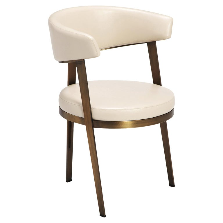 Available as a set of six, this high end set of dining chairs features a timeless design with sleek, modern curves. Each seat is upholstered in modified faux cream leather for durability and finished in antique bronze details. The sophisticated look