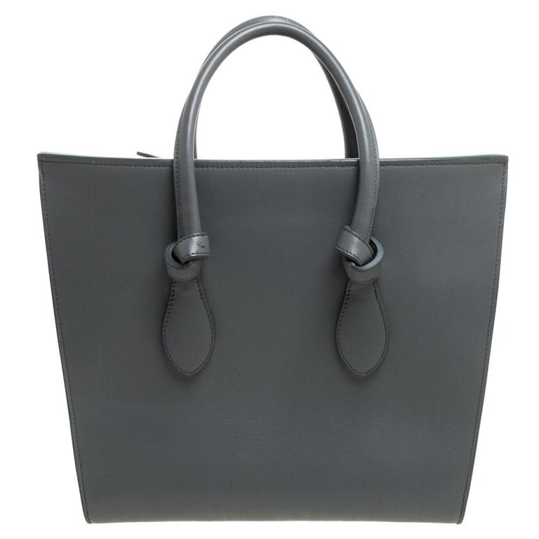 This Tie tote from Celine brings a wonderful mix of fashion and function. Expertly crafted from leather, it comes in a lovely shade of grey with dual top handles and metal studs to protect the base. Made in Italy, it has a spacious interior lined