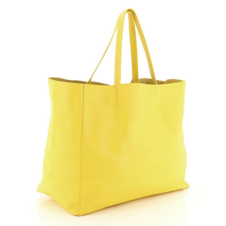 This Celine Horizontal Cabas Tote Leather Large, crafted in yellow leather, features dual flat leather handles, stamped Celine logo at the center, and gold-tone hardware. Its wide open top showcases a yellow raw leather interior with zip pocket.
