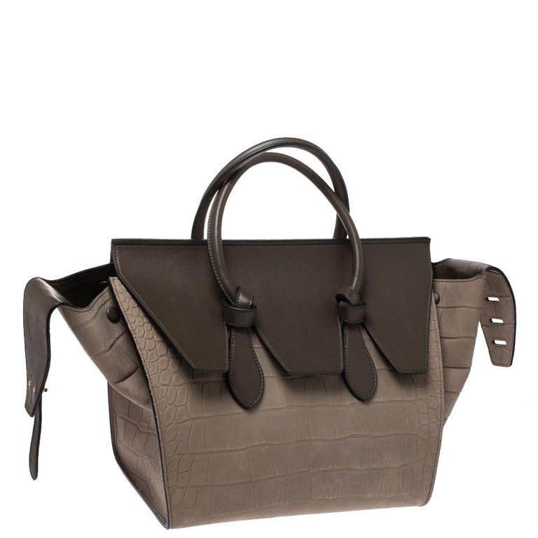 This Tie Knot tote from Celine brings a wonderful mix of fashion and function. Expertly crafted from croc-embossed leather, it comes in a lovely shade of khaki with dual top handles and metal studs to protect the base. Made in Italy, it has a