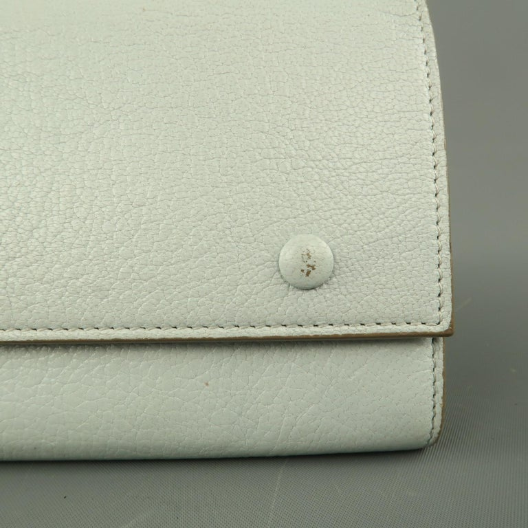 CELINE checkbook wallet comes in light blue textured leather with taupe trim, rectangular shape, flap with snap closures, gold foil logo, and dual compartments with zip pouch divider. Minor wear. Made in Italy.   Very Good Pre-Owned Condition.