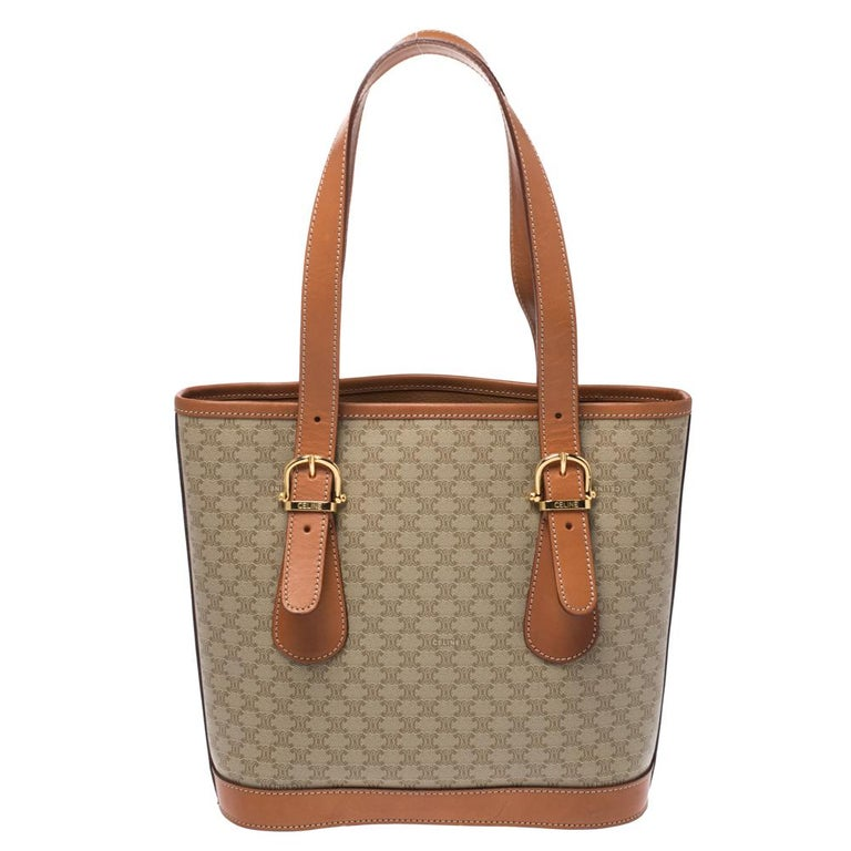 This light brown tote from Celine will give you days of style and ease. It is crafted from Macadam coated canvas as well as leather and features a simple design. It is equipped with a well-lined interior, two leather handles and gold-tone
