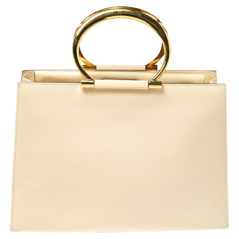 Swing this light cream-hued beauty in style. The creation is from Celine, made from leather in a structured silhouette and equipped with a sizeable fabric interior. The tote features two metal ring handles and metal studs to protect the base.