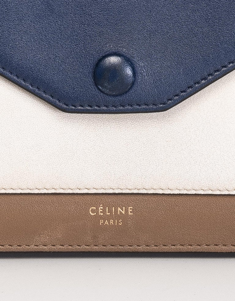Celine wallet made of cream and brown leather with a blue flap with snap closure. The interior has brown leather with three compartments; two for cards and one middle zipper coin pocket.  COLOR: Blue, cream and brown MATERIAL: Leather DATE CODE: