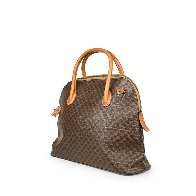 Brown and tan Macadam coated canvas Celine Vintage Satchel with  – Gold-tone hardware – Single flat detachable shoulder strap – Dual roll top handles – Protective feet at base – Cognac leather trim; tan leather lining, single interior zip pocket and