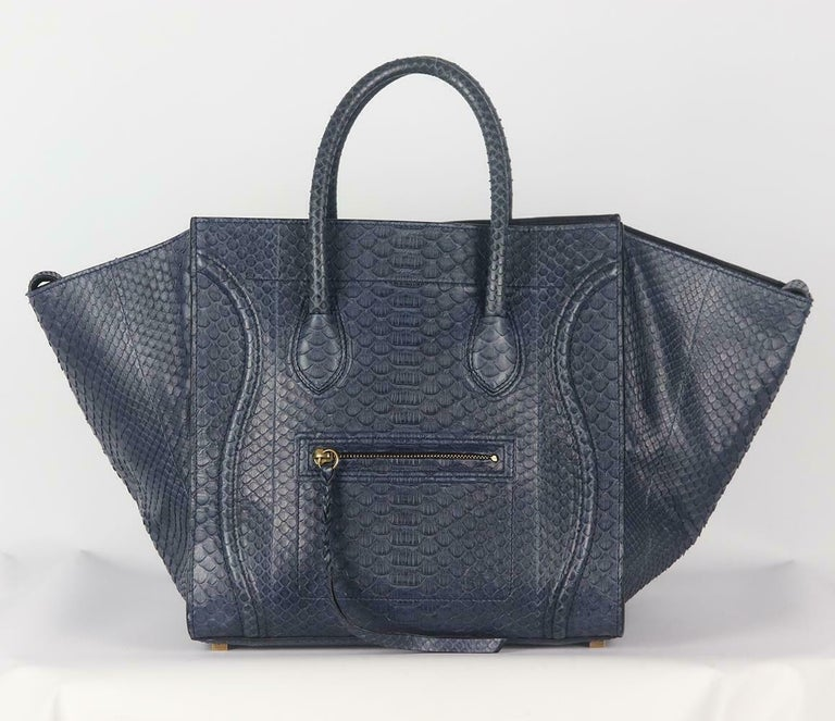 This flawlessly bag is crafted in rich navy python and leather phantom luggage tote bag has been part of Celine's timeless collection, it's designed with internal pockets and an oversized external flaps which can be pulled in to ensure your