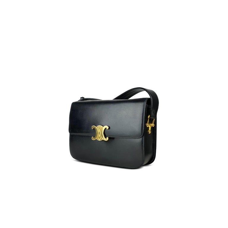 Black calfskin Celine Medium Triomphe bag with  - Gold-tone hardware - Single flat adjustable shoulder strap - Three interior compartments - Tonal lambskin leather lining, dual pockets at interior walls; one with zip closure and Triomphe push-lock