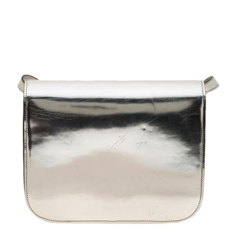 From the house of Celine comes this gorgeous Classic Box flap bag that will perfectly complement all your outfits. It has been luxuriously crafted from metallic silver leather and styled with a flap that opens to a well-sized leather interior. The